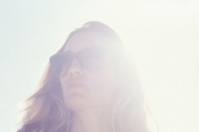 Woman wearing Mykita Luna sunglasses in the sun with lens flare