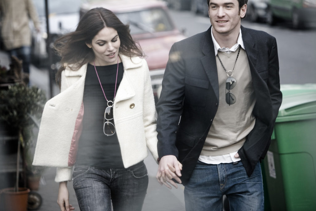 Woman and Man wearing La Loop necklaces with sunglasses and holding hands